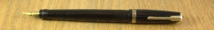 A small black pen with a gold (tone) point